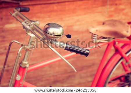 Vintage bicycle with wood wall background. - stock photo