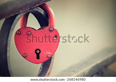 vintage  big padlock of red color is fixed in the locked state on an iron fence and has a keyhole, the digital photo with a retro effect, blank space for the text, - stock photo
