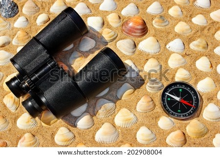 Vintage Binoculars, Compass and Seashells on a Beach Sand close-up. Summer Marine background with space for text or image