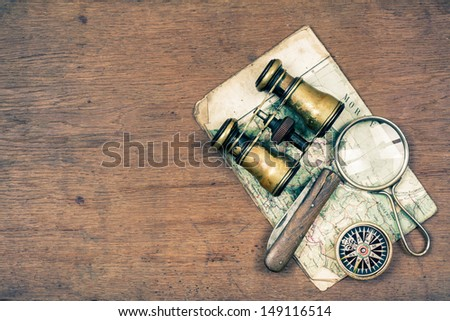 Vintage binoculars, compass, old map, magnifying glass, pocket knife on wooden background - stock photo