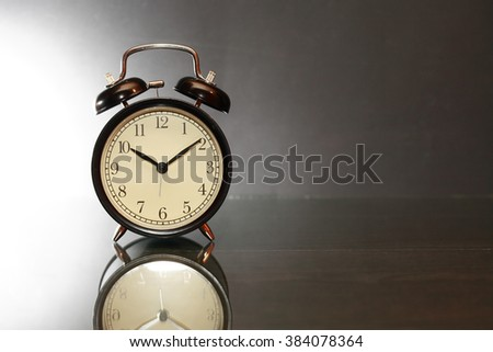 Vintage black alarm clock on dark background with free space for text
