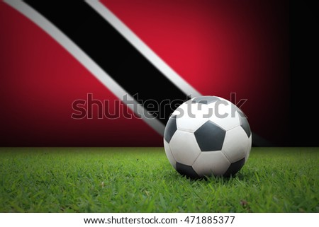 vintage black and white football ball on green grass has the national flag of Trinidad and Tobago background
