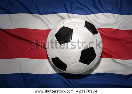 vintage black and white football ball on the national flag of costa rica - stock photo
