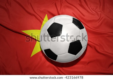 vintage black and white football ball on the national flag of vietnam