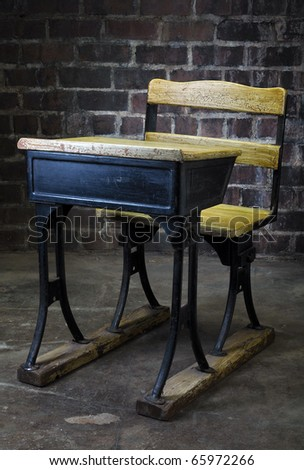 Vintage black and yellow crack paint old school desk with brick background - stock photo