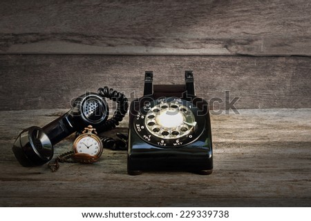 Vintage black dial analog telephone and pocket watch on old grunge wood atmosphere - stock photo