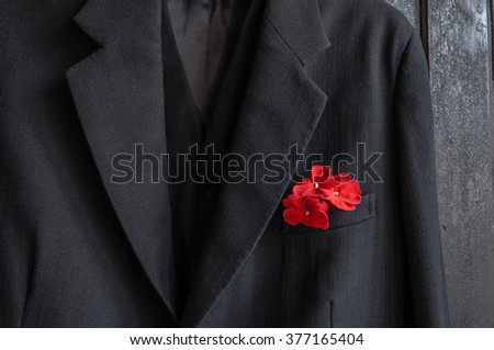Vintage black jacket with a red flower in its pocket on the black wardrobe