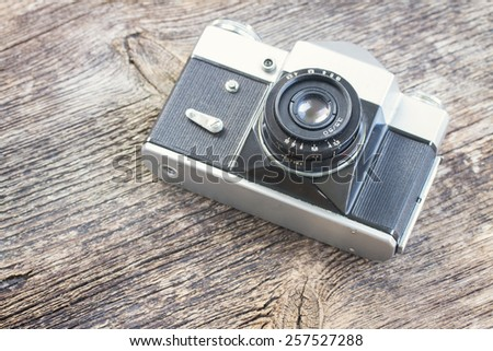 vintage black photo camera on wooden background, retro toned - stock photo