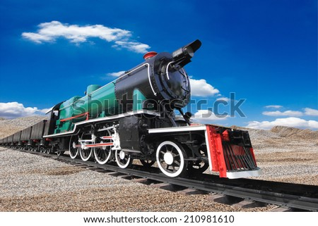 vintage black steam powered railway train against blue sky background  - stock photo