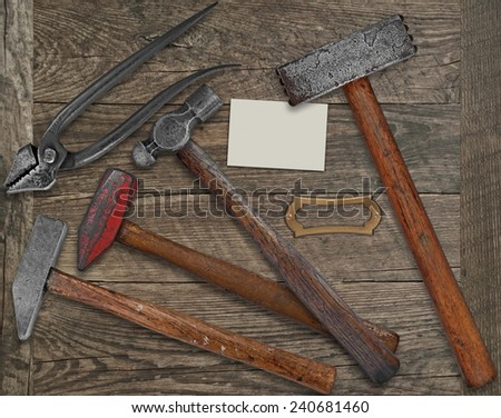 vintage blacksmith or metalwork tools over wooden bench, blank plate and business card for your text - stock photo