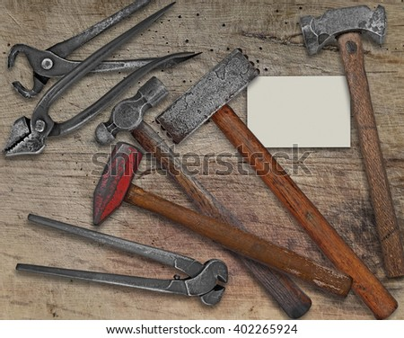 vintage blacksmith or metalwork tools over wooden bench,  business card for your text - stock photo