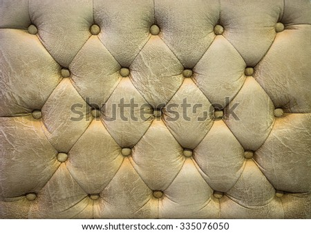 Vintage blond color upholstery buttoned sofa (background) - stock photo