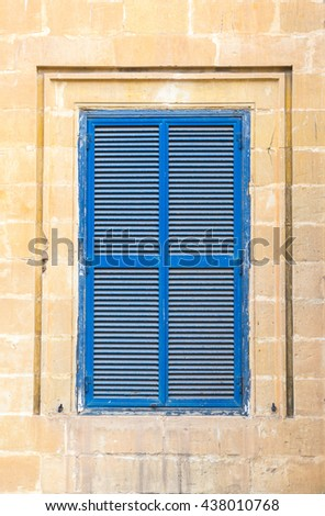 Vintage blue close window with shutters in old yellow limestone wall. Malta, Mdina. Good for 3d models texture. Outdoor. - stock photo