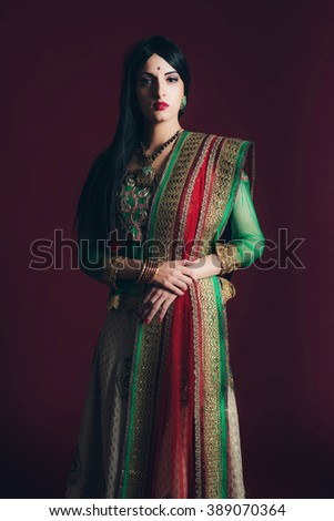Vintage Bollywood fashion girl against dark red background. - stock photo