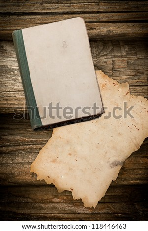 Vintage book and paper sheet on a wooden background