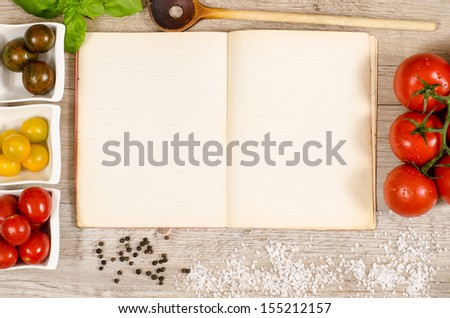 Vintage book and paper with text space for ingredients of a recipe on a wooden table