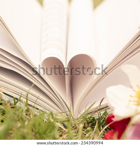 Vintage book heart shape on grass, dept of field. - stock photo