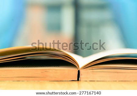 Vintage book on wooden table beside window - stock photo