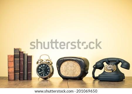Vintage books, alarm clock, old radio, retro telephone on wood table - stock photo