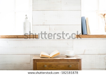 Vintage books and coffee cup on furniture - stock photo