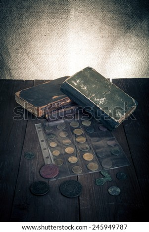 Vintage books and coins on old wooden table. Toned.
