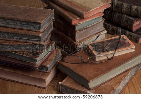 Vintage books are stacked on a wooden table with a pair of reading glasses on top. - stock photo