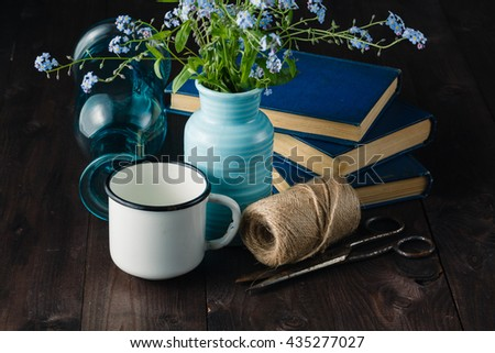 Vintage books on table with forget me not flowers. nostalgia concept
