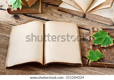 Vintage books. Open blank book on wooden desk with autumn maple leaves close up. Copy space. Free space for test - stock photo