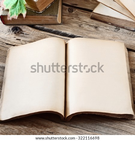 Vintage books. Open blank book on wooden desk with autumn maple leaves close up. Copy space. Free space for test. Square frame - stock photo