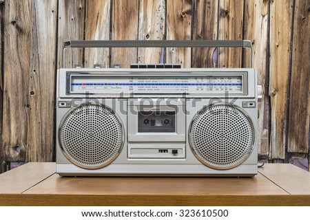 Vintage boombox on wood table with rustic cabin wood wall. - stock photo