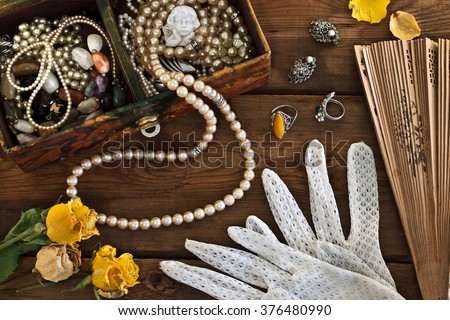 Vintage box with trinkets and jewelry on wooden background