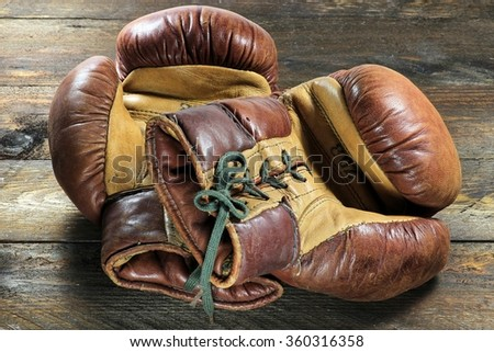 vintage boxing gloves on wooden background - stock photo