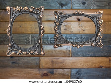 Vintage brass frames on old brown wooden background with horizontal boards - stock photo