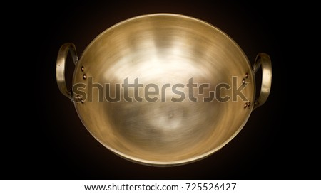 Vintage Brass pan on black background with embedded clipping path, the surface with gold shiny from natural light, image seen from top view, beautiful texture inside.