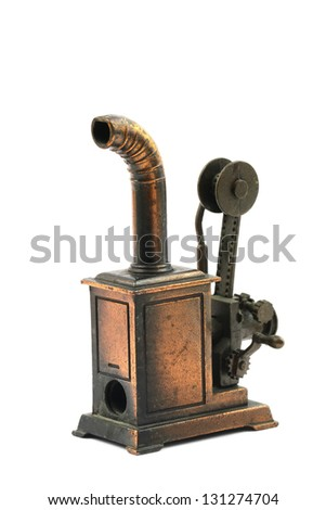 Vintage brass pencil sharpener in shape of machine isolated on white