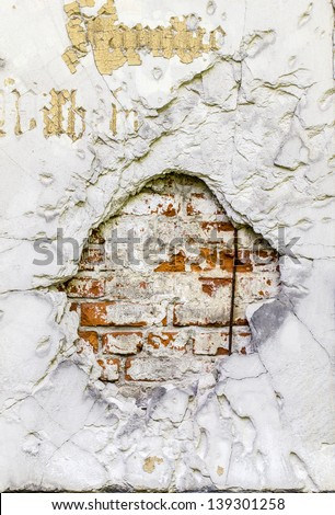 vintage brick rendered wall background with big bullet hole - stock photo