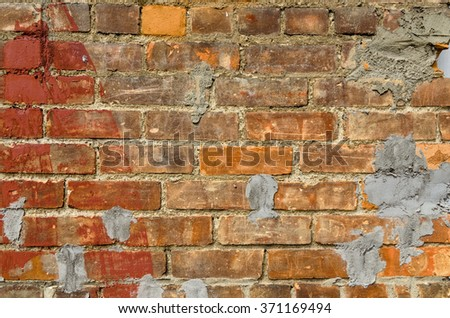 Vintage Brick Wall Badly Patched with Cement - stock photo