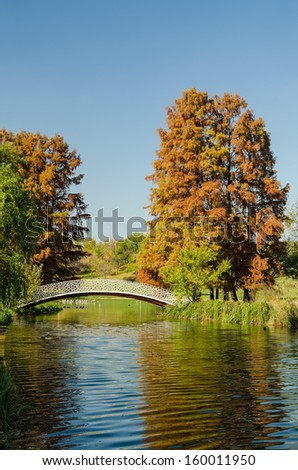 Vintage Bridge Over Lake With Late October Autumn Colors