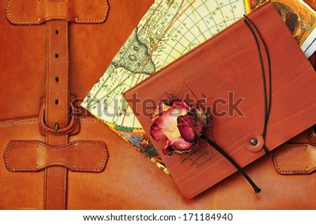 Vintage briefcase with map, dry rose and note  - stock photo