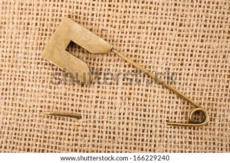 Vintage brooch or safety pin on jute background, - stock photo