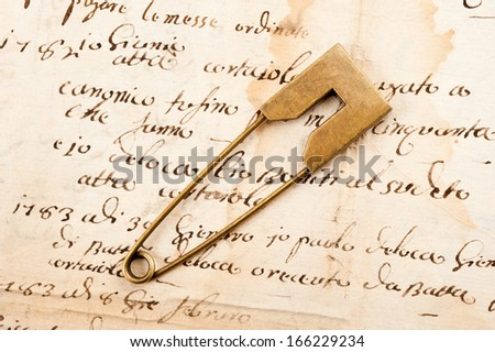 Vintage brooch or safety pin on letter background, - stock photo