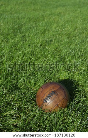 Vintage brown football soccer ball sits in bright sunny green grass field - stock photo