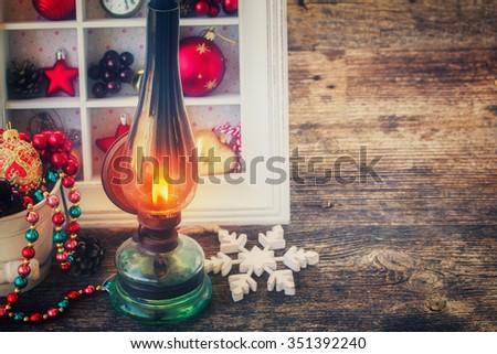 vintage burning  lantern with  christmas decorations, low key, retro toned - stock photo