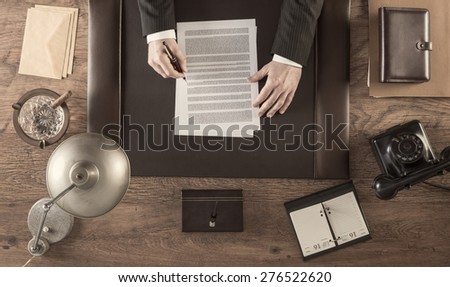 Vintage businessman in the office reading and signing a contract sitting at his desk, top view - stock photo