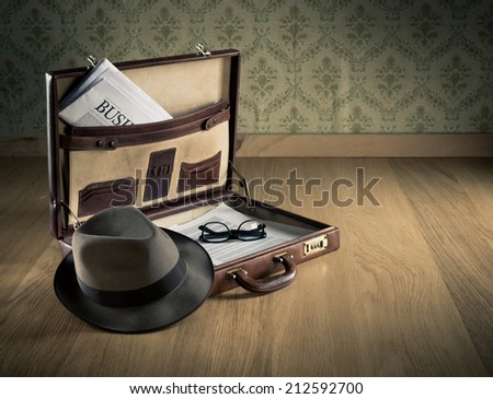 Vintage businessman open briefcase on the floor with financial newspaper and hat. - stock photo