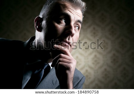 Vintage businessman with pensive expression on retro wallpaper background. - stock photo