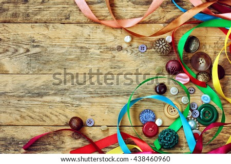 vintage buttons and multicolored ribbons lie on old wooden table - stock photo