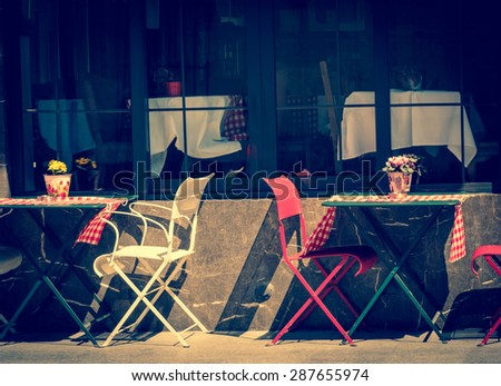 Vintage cafe exterior. Street food at retro style. Cafe with tables and chairs in an old street, toned image of the retro vintage Instagram style filter effect. - stock photo
