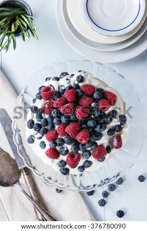 Vintage cake stand with Meringue dessert Pavlova with fresh blackberries and raspberries. Over blue wooden table with old tableware, textile napkin and snowdrops flowers. Flat lay - stock photo