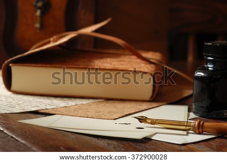 Vintage calligraphy pen with leather bound journal and writing supplies on antique desk.  Closeup with natural, warm sunlight and shallow dof.  Selective focus limited to pen.